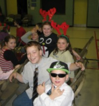 Students at Christmas Concert, some wearing reindeer antlers