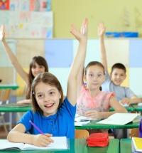 Students with hands raised to answer a question