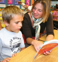Volunteer parent reading to a student
